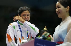 FILE – In this Wednesday, Oct. 1, 2014 file photo, India's L. Sarita Devi cries looking at a medal after she refused to accept her bronze medal during the medal ceremony for the women's light 60-kilogram division boxing at the 17th Asian Games in Incheon, South Korea. Devi has been provisionally suspended on Wednesday, Oct. 22, by boxing's international governing body for rejecting her Asian Games bronze medal at the podium following her controversial semifinal loss at Incheon. (AP Photo/Kin Cheung, File)