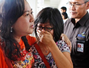 A relative of AirAsia flight QZ 8501 passengers weep as she waits for thelatest news on the missing jetliner at Juanda international Airport in Surabaya.Dec 28 2014.
