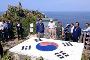 South Korean President Lee Myung-bak (c.) looks at a national flag upon his arrival at islands called Dokdo in Korea and Takeshima in Japan.