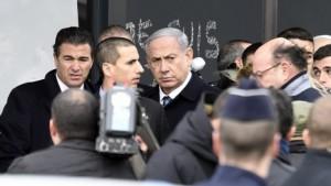 Prime Minister Benjamin Netanyahu (R) arrives at a kosher grocery store in Porte de Vincennes, eastern Paris, on January 12, 2015.