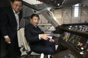Chinese President Xi Jinping (R) sits in the cockpit of a model of a C919 passenger jet as he visits the design and research center of Commercial Aircraft Corporation of China in Shanghai, May 23, 2014