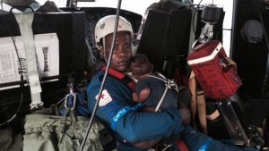 Baby Yudier Moreno was held by a rescuer on the flight back to Quibdo