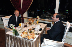 Russian President Vladimir Putin (L) and Egyptian President Abdel Fattah al-Sisi smile during their dinner in Cairo February 9, 2015.