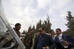 Yemeni politicians Yasser al-Awadi (C) and Hamza al-Houthi (R) board a United Nations plane to Geneva for UN-led talks on the Yemeni crisis, at the international airport of Sanaa