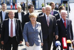 Heidenau major Juergen Opitz, German Chancellor Angela Merkel, Saxony State Prime Minister Stanislaw Tillich and President of the German Red Cross Rudolf Seiters (LtoR) arrive for statements after their visit to an asylum seekers accomodation facility in the eastern German town of Heidenau near Dresden, August 26, 2015.