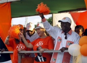 Ivory Coast's President Alassane Ouattara of the Rally of the Houphouetists for Democracy and Peace (RHDP) party and his wife Dominique Ouattara  wave during his last campaign rally, ahead of the October 25 presidential election, in Abidjan October23, 2015.