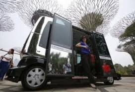 Members of the media disembark from an autonomous self-driving vehicle during a demonstration at Gardens by the Bay in Singapore October 12, 2015.