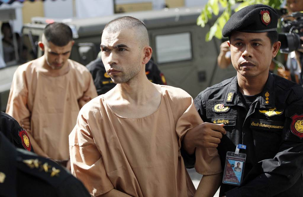 Police officers escort Bilal Mohammad (center front) and Mieraili Yusufu,  the two suspects