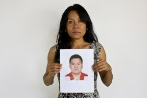 , Adriana Bahena Cruz holds up a photo of her husband, Saulo Rodriguez Cruz, in Iguala, Mexico. Bahena's husband was a detective with the state prosecutor's office in Iguala. On Jan. 7, 2011, he was in downtown Iguala with his wife and children when he received a call saying there was a development in one of his cases and he needed to come into the office. His wife awoke at 2 a.m. to find he was still not home. When she called him he answered, but she heard the voices of a lot of other men in the background. He said he would be home soon. She never heard from him again.