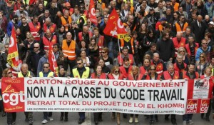 """French labour union workers and students attend a demonstration against the French labour law proposal in Marseille, France, as part of a nationwide labor reform protests and strikes, March 31, 2016. The slogan reads """"No to the break-up of the labour law. Withdrawal of El Khomri law"""" on a banner surrounded by CGT labour union flags."""