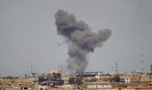 A plume of smoke rises above a building during an air strike in Tikrit.