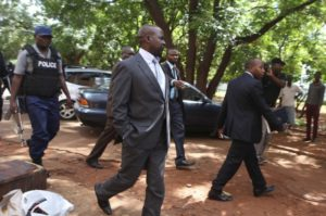 Zimbabwe's Prosecutor General Johannes Tomana (C) arrives escorted by policemen at the Harare Magistrates court, February 2, 2016.