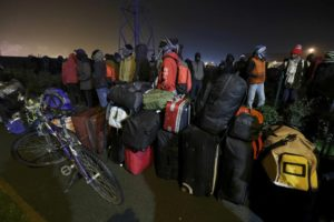 """Migrants with their belongings queue as their evacuation and transfer to reception centers in France, and the dismantlement of the camp called the """"Jungle"""" in Calais, France, starts October 24, 2016."""