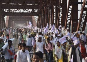 Hindu pilgrims hold religious flags and walk on a crowded bridge after a stampede on the same bridge on the outskirts of Varanasi, India, Saturday, Oct. 15, 2016. More than a dozen people were killed and several more injured in a stampede that occurred as they were crossing a crowded bridge Saturday to reach the venue of a Hindu religious ceremony in northern India.